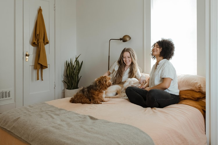 Two ladies on the bed with their pet dog